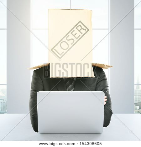 Cardboard box with 'loser' stamp on the head of a businessperson using laptop at workplace. Failure concept. 3D Rendering