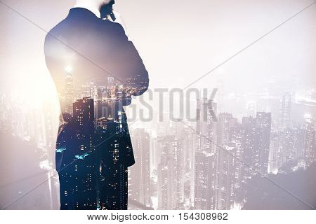 Back view of thinking business man in suit on night city background. Research concept. Double exposure