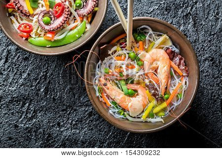Chinese noodles with vegetables and seafood on black rock