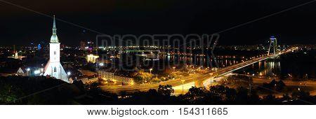 Night photography of illuminated city, church, river and bridges in Bratislava