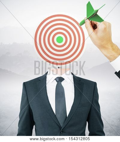 Hand with green dart aiming at target-headed businessman on landscape background. Aiming and targeting concept