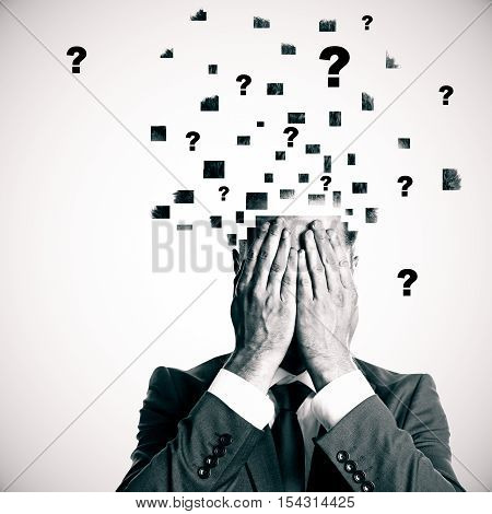 Businessman with broken into pieces head and abstract question marks on light background. Confusion concept