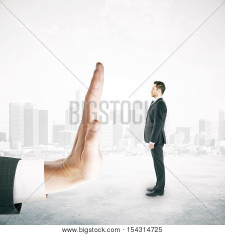 Tiny man in suit standing against human palm on city background. Denial concept