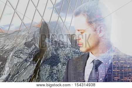 Sad pensive businessman behind iron wire mesh on landscape background. Freedom concept