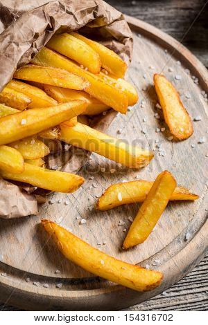 Homemade French fries made ​​from potatoes on wooden table
