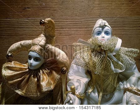 Two porcelain harlequin puppet on a wooden background
