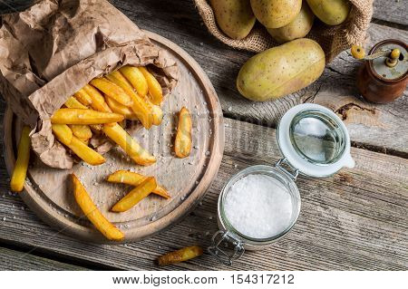 Homemade fries made of fresh potato on wooden table