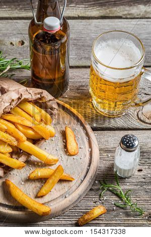 Fresh french fries served with beer on wooden table