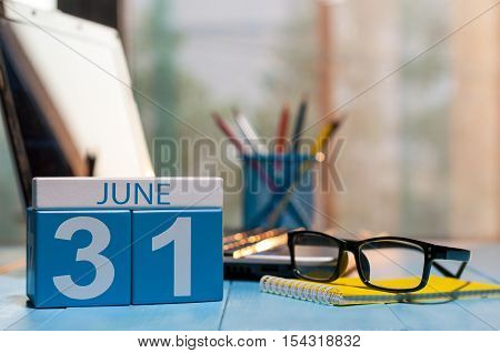 June 31th. Day 31 of month, back to school time. Calendar on student or teacher workplace background. Summer end. Empty space for text.