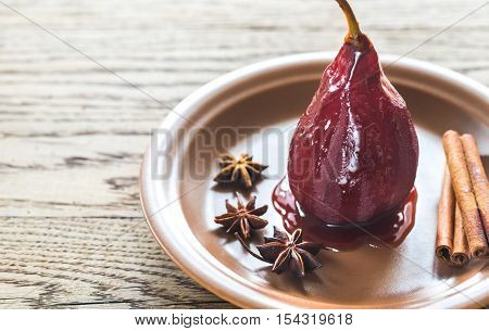 Merlot-poached pear with spices on the plate