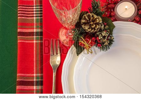 Christmas table setting with porcelain plates fork wineglass and burning candle. Top view. Horizontal.