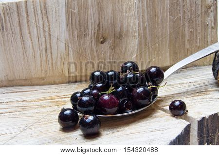 Currant.  On Spoon And Wooden Background.