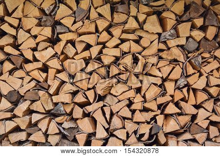 Firewood stacked in a woodpile close-up for the background.