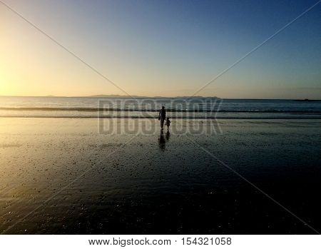 Grandmother and grandchild walks on the beach during summer holiday on sunset.