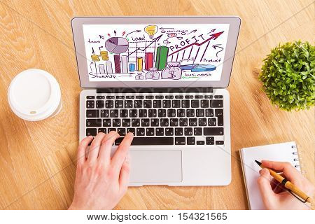 Hand using laptop with creative business sketch and writing in spiral notepad placed on wooden desktop with coffee cup and decorative plant. Financial growth concept