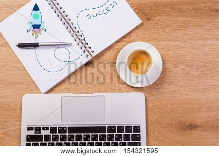Top view of wooden desktop with laptop keyboard coffee cup and spiral notepad with creative rocket drawing. Business start up concept. Mock up