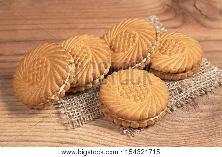 Cookie round with milk filling on old wooden table