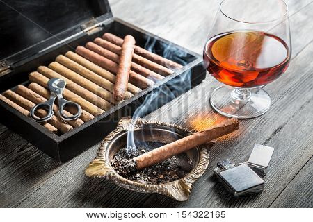 Aroma of cognac and cigar fuming on wooden table