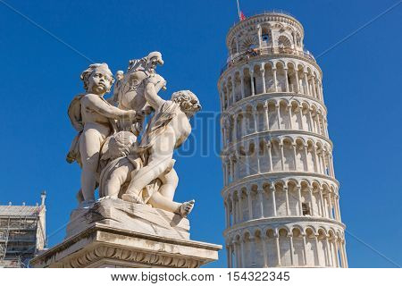 PISA, ITALY - SEPTEMBER 2016 : Leaning Tower of Pisa and status of cherubs winged angels in Pisa, Italy on September 22, 2016. Torre pendente di Pisa is freestanding bell tower campanile of cathedral