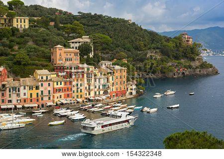 PORTOFINO, ITALY - SEPTEMBER 2016: Boats ships docking, departure near restaurants, shops, colorful historical buildings at Portofino port, fishing village, Genoa province, Italy on September 23, 2016