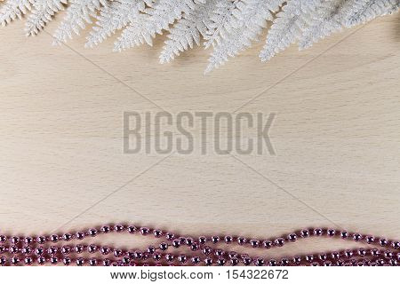 white fern and pink beads on a wooden background