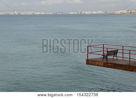 Empty footbridge with a bench over the sea