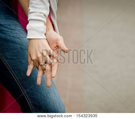 A young couple holding hands outdoors. Shallow depth of field