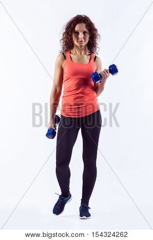 Sport woman in active wear is exercising with dumbbells on white background