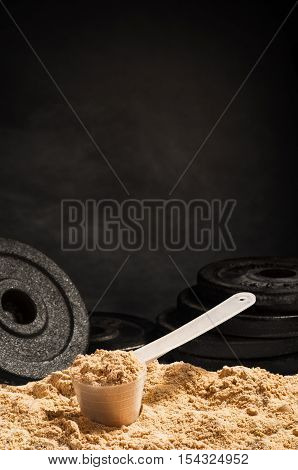 Product photograph of spoon or measuring scoop of whey protein on black chalkboard background