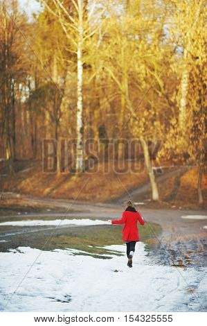 Young girl in a red coat flees waving his arms on a snowy road in the Park