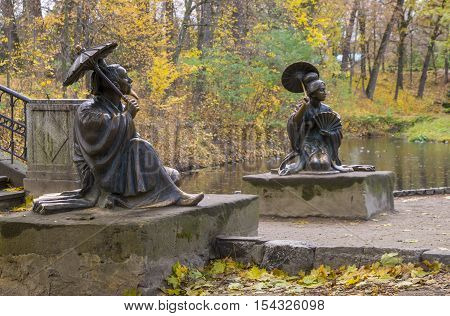 Two chinese statues near the lake in the autumn park