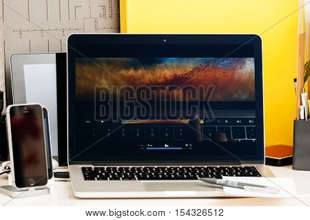 PARIS FRANCE - OCT 28 2016: Apple Computers website on new MacBook Pro Retina with OLED Touch bar in geek creative room showcasing Apple Keynote presentation of image editing on macbook pro display oled