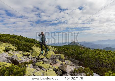 Girl stands on the rocks at the top of the mountain. Nature