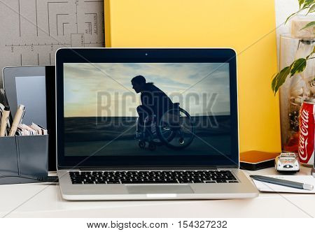 PARIS FRANCE - OCT 28 2016: Apple Computers website on new MacBook Pro Retina with OLED Touch bar in geek creative room showcasing Apple Keynote presentation of Accesibility wheelchair movie