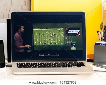 PARIS FRANCE - OCT 28 2016: Apple Computers website on new MacBook Pro Retina with OLED Touch bar in geek creative room showcasing Apple Keynote presentation of Tv app by Apple Nfl game