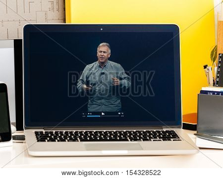 PARIS FRANCE - OCT 28 2016: Apple Computers website on new MacBook Pro Retina with OLED Touch bar in geek creative room showcasing Apple Keynote - Philip Schiller speaking