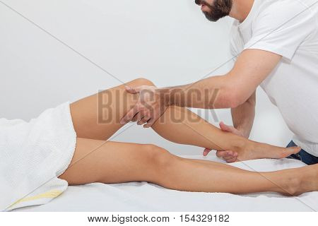 masseur massaging a patient on leg