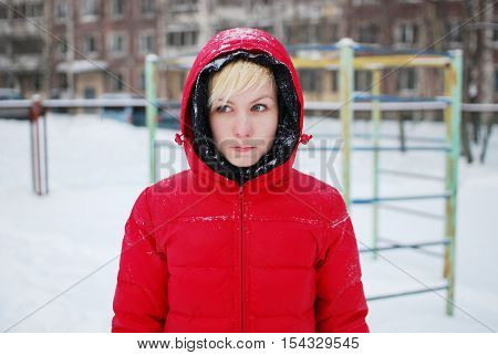 A young girl in a red hooded jacket stands in a St. Petersburg yard in the Playground snowflakes falling on her face and melt.