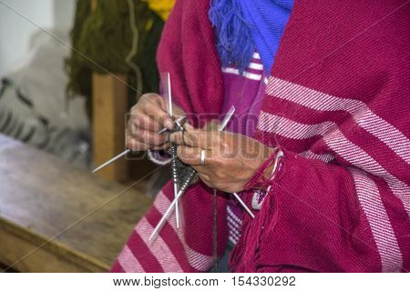 Close-up of a hands knitting. Lady in a sewing plant, outskirts of Guaranda, Bolivar province, Ecuador
