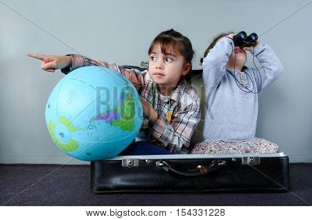 Two children (girls age 02 and 06) playing at home a kids traveler game in a travel suitcase. Children travel holiday vacation and trip concept.
