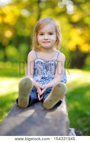 Adorable little girl playing outdoors on summer day