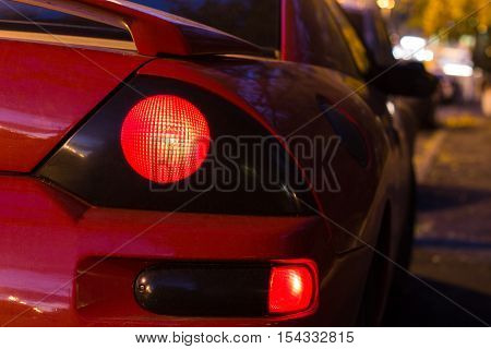 Red sports car glowing Back Lights at night. back view
