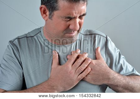 Man having acute pain in a his chest . Close up of Middle age male. real people. copy space