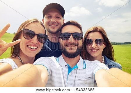 A mid shot of four people wearing light clothes and sunglasses make a selfie outdoors with smiles on their face. Green meadow and grey sky behind them