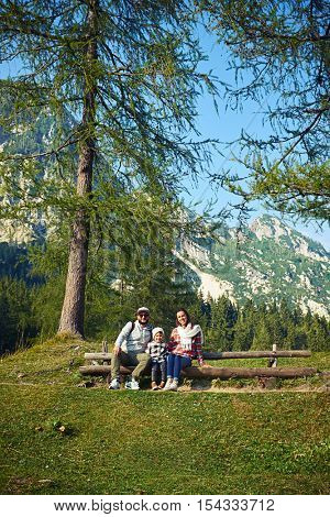 young family sitting on the bench while posing at the camera. Wearing casual clothes. Wooden bench is located on a grassy blade, surrounded by forest and mountains