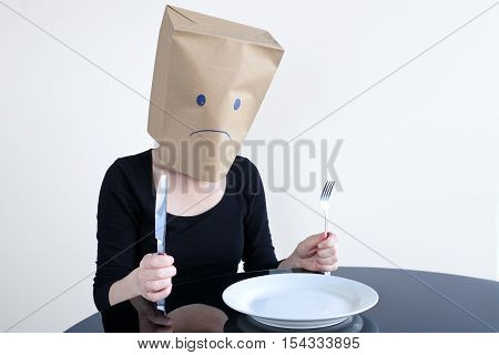 Anonymous Sad Woman With Empty Plat Sit At The Table Alone