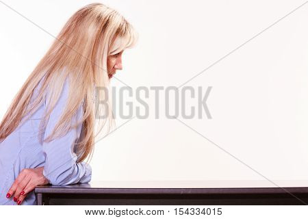 Relax free time waiting and thinking. Middle aged woman with long blond hair sit at table thoughtful.