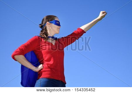 Superhero mother against blue sky background with copy space. concept photo of Super hero girl powerparenthood and motherhood. Real people