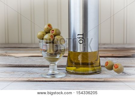 horizontal image of two focused olives on a fork with a dish of olives and a bottle of olive oil blurred in the background on a wood background