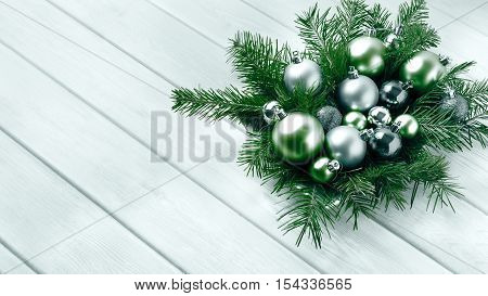 Christmas table centerpiece with silver and green ornaments. Christmas party decoration with shiny balls. Christmas greeting background. Copy space.